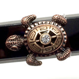 Closeup of Fitband Bling Sea Turtle two-tone gold and copper metal and rhinestone charm on Fitbit Alta band