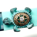 Closeup of Fitband Bling Sea Turtle two-tone gold and verdigris metal and rhinestone charm on Fitbit Flex band