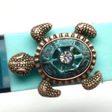 Closeup of Fitband Bling Sea Turtle two-tone verdigris and gold metal and rhinestone charm on Fitbit Flex band