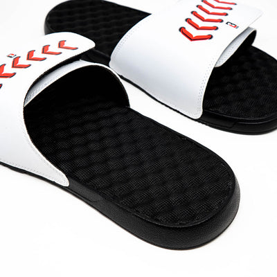 Closeup of red stitching on white slide sandals with black bottom