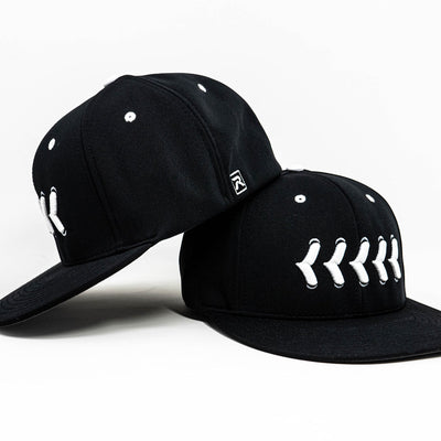 Side view of fitted black hat with white baseball stitching