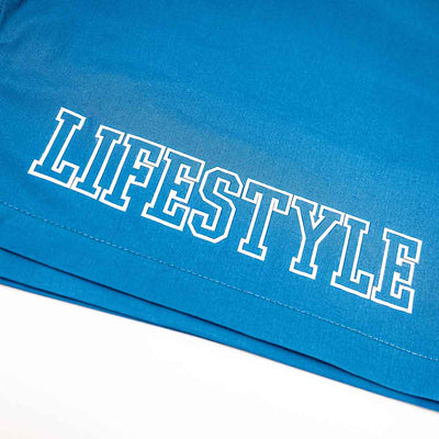 Closeup of LIFESTYLE graphic on blue shorts