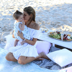 michelle alan and daughter harper sitting on picnic blanket on beach