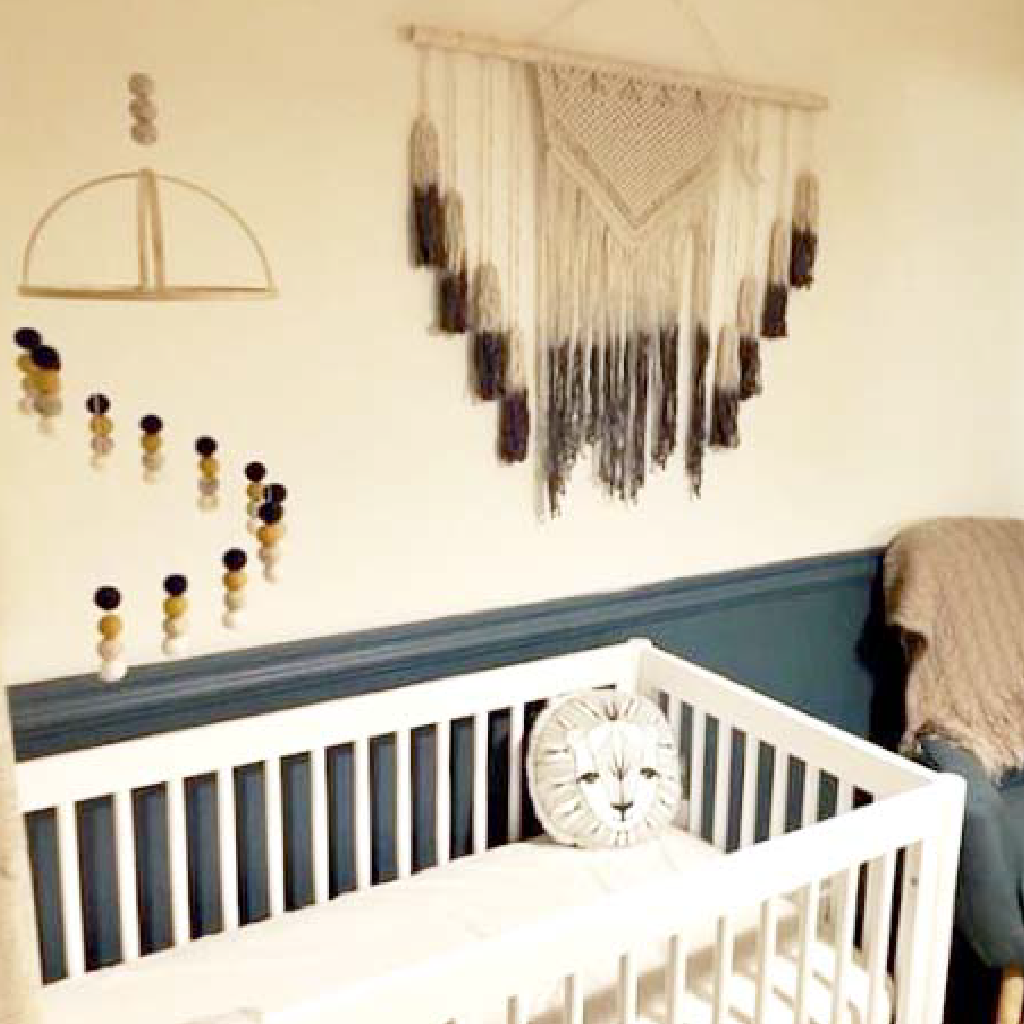 boho nursery with wall hanging and pom pom mobile