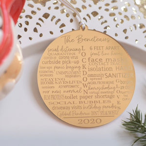Gold 2020 pandemic ornament on a white plate with greenery