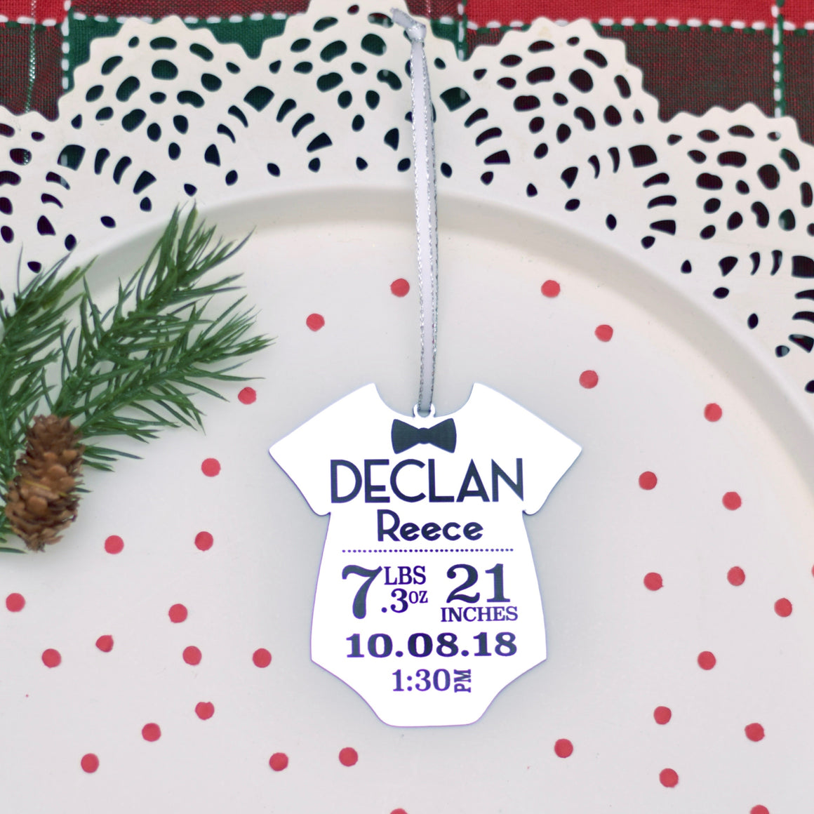 Silver onesie Christmas ornament with Baby stats in black placed onto a white cake plate with some Christmas greenery and red confetti