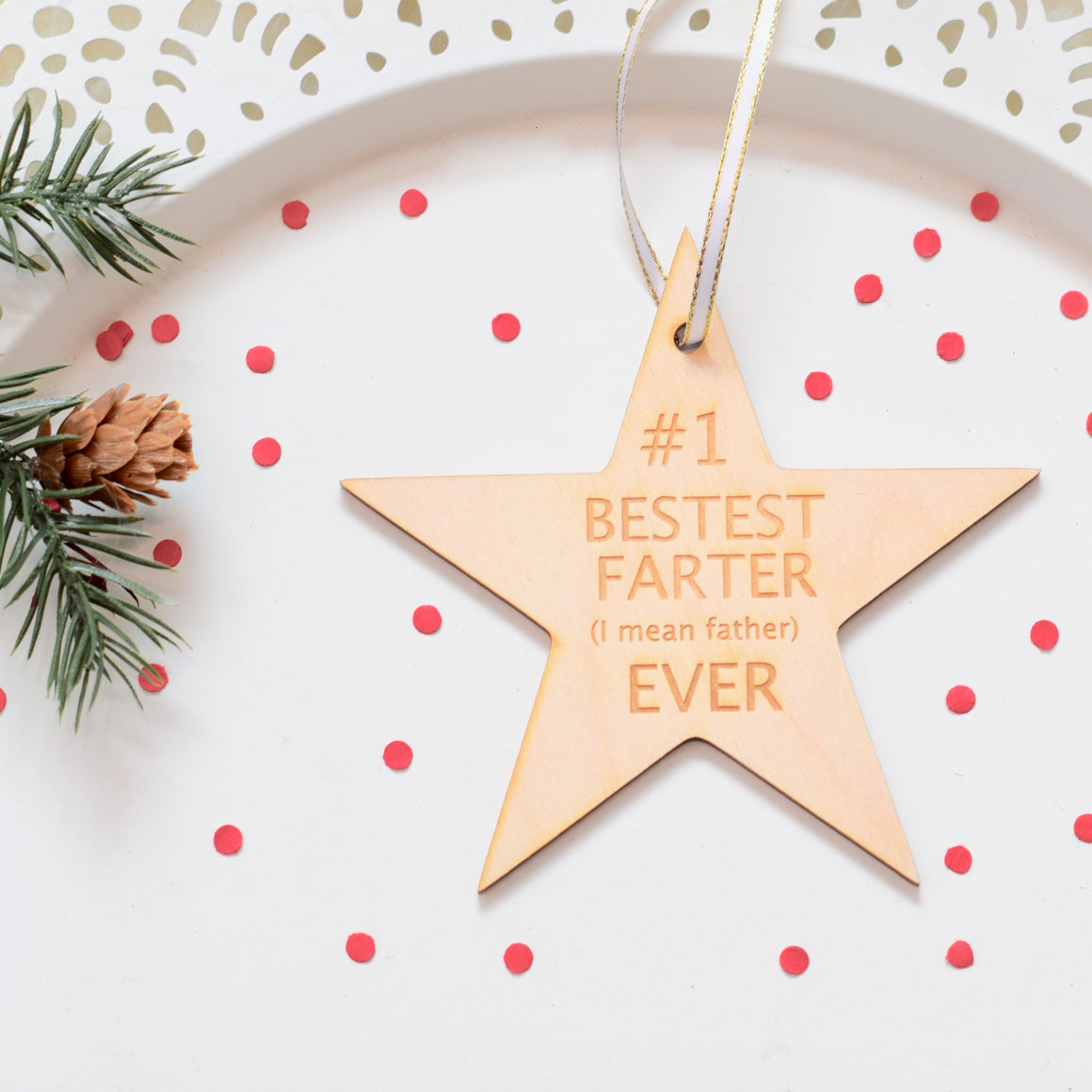 Star Christmas Ornament that says #1 bestest farter (I mean father) ever placed on a white plate with confetti