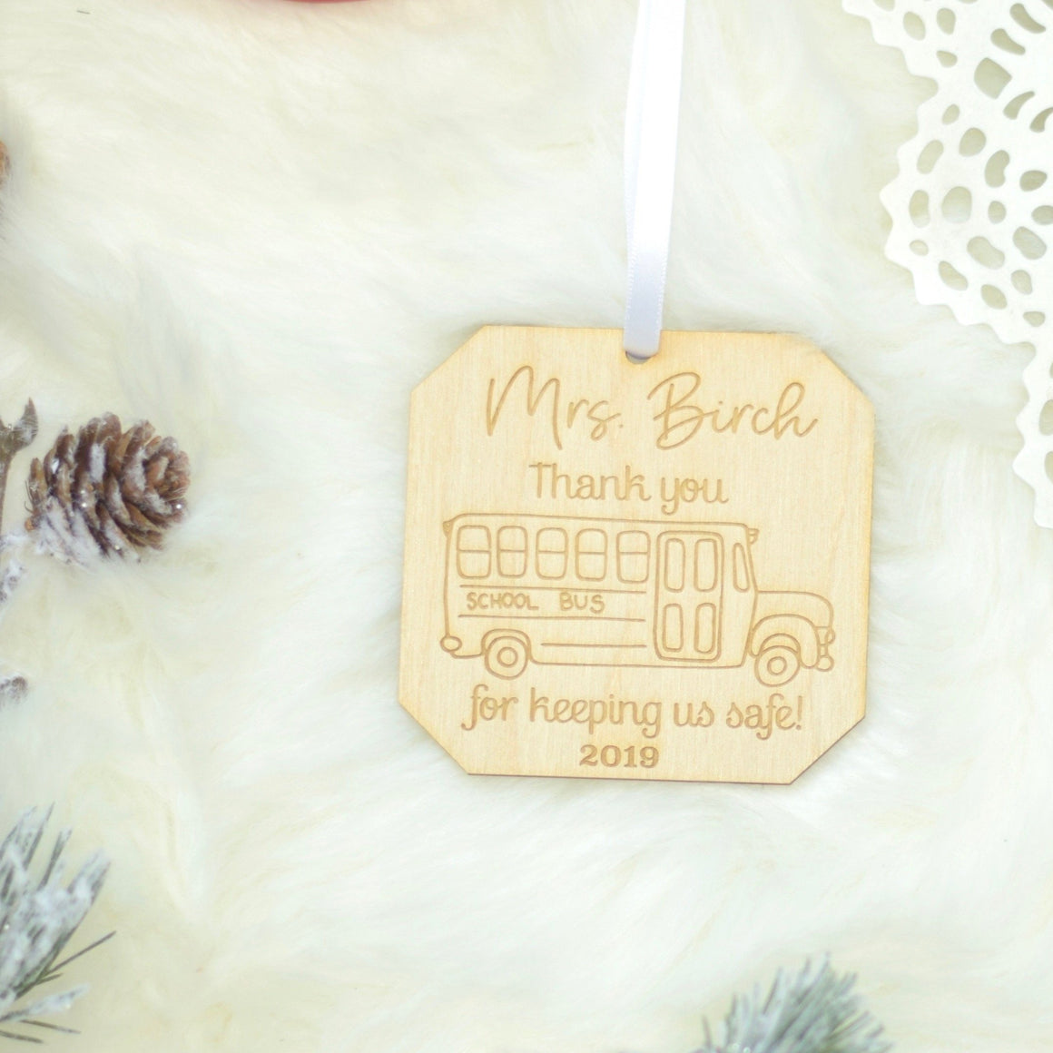 Mrs Birch Thank you for keeping us safe Christmas ornament with a bus. Lying on a piece of white fur with decorations around it