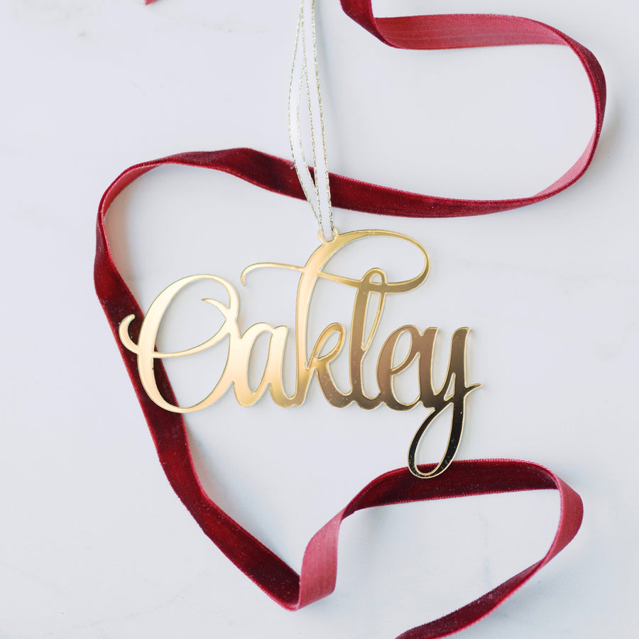 Oakley gold name Christmas ornament with red ribbon around it