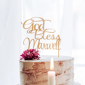 god bless Maxwell cake topper with a candle in front of white cake at a baptism