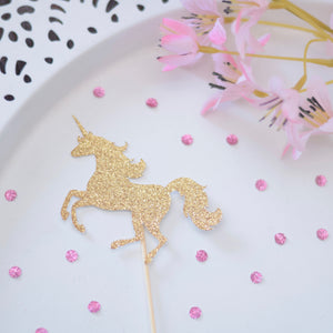 Sparkly gold unicorn cupcake topper on a white plate with pink flowers