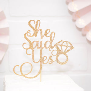 gold she said yes cake topper on a white cake and pink decorations