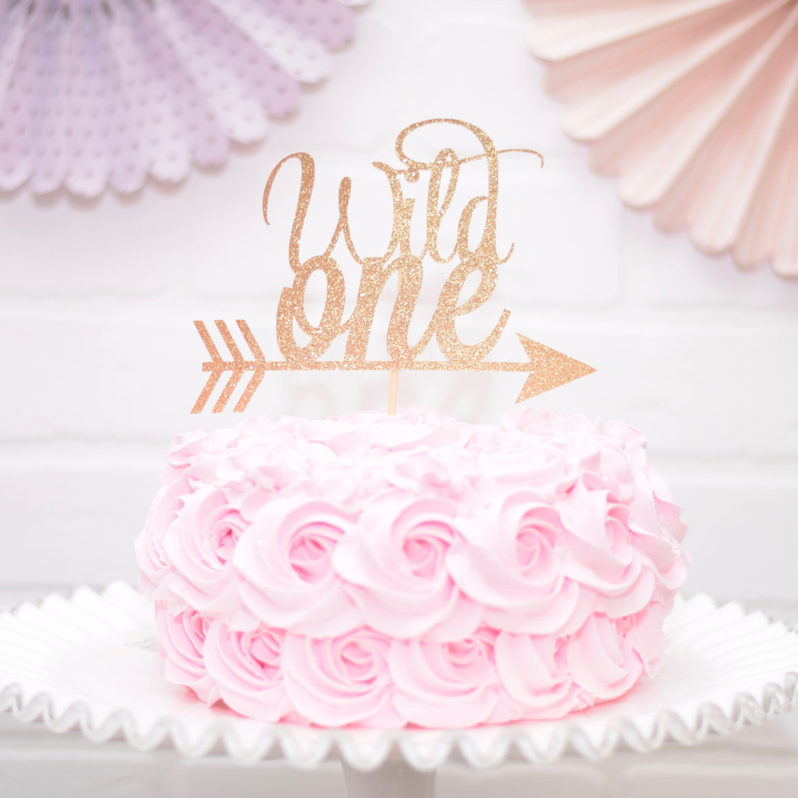 Gold wild one cake topper on pink rosette cake