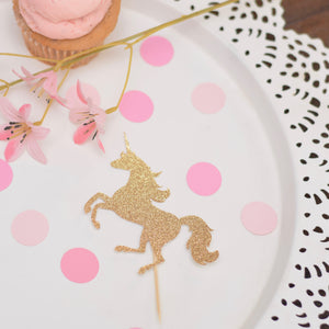 Sparkly gold unicorn cupcake topper with pink cupcake, pink flowers and pink circle confetti.