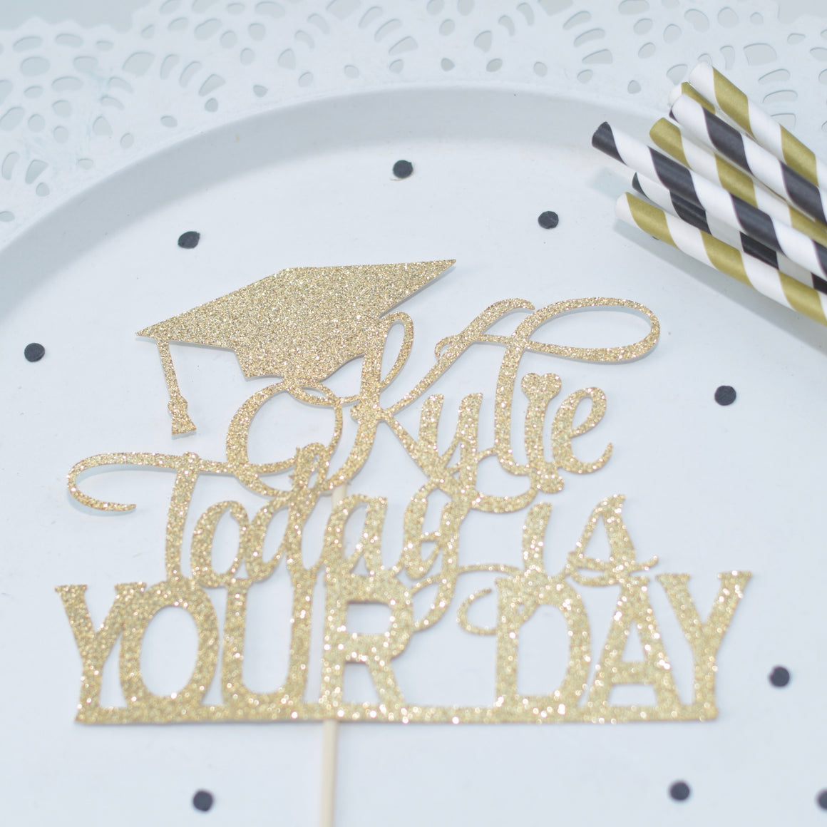 Black and gold graduation decorations straws and cake topper with confetti