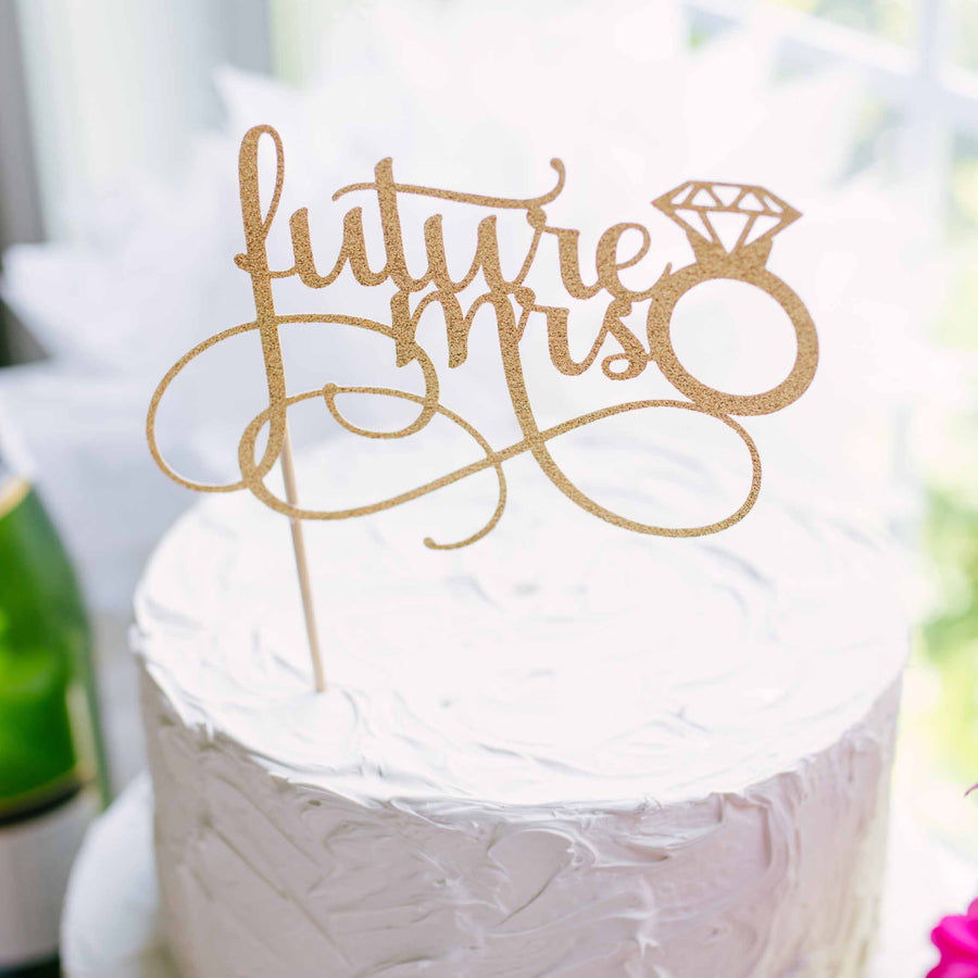 Gold future mrs cake topper on a white cake and flowers