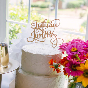 Gold Futura Señora Cake Topper on cake with champagne and flowers