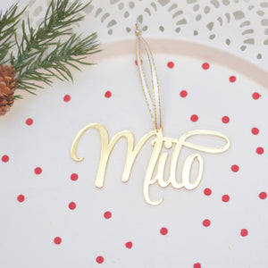 Milo gold Christmas tree ornament lying on a white cake plate with greenery and red confetti