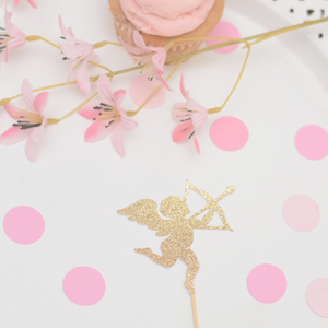 Gold cupid cupcake toppers on a cake plate with pink flowers and a cupcake