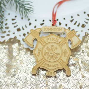Fire Department ornament made out of wood on a sparkly gold table cloth