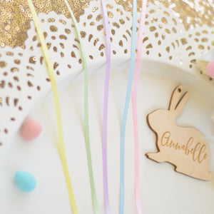 Yellow, gree, purple, blue and pink ribbon on a white tray with an Easter basket tag