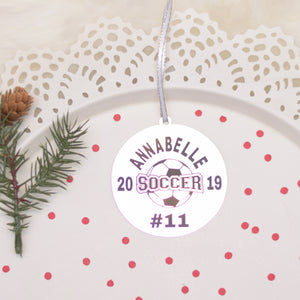 Round silver soccer ornament on a cake plate with red confetti and greenery