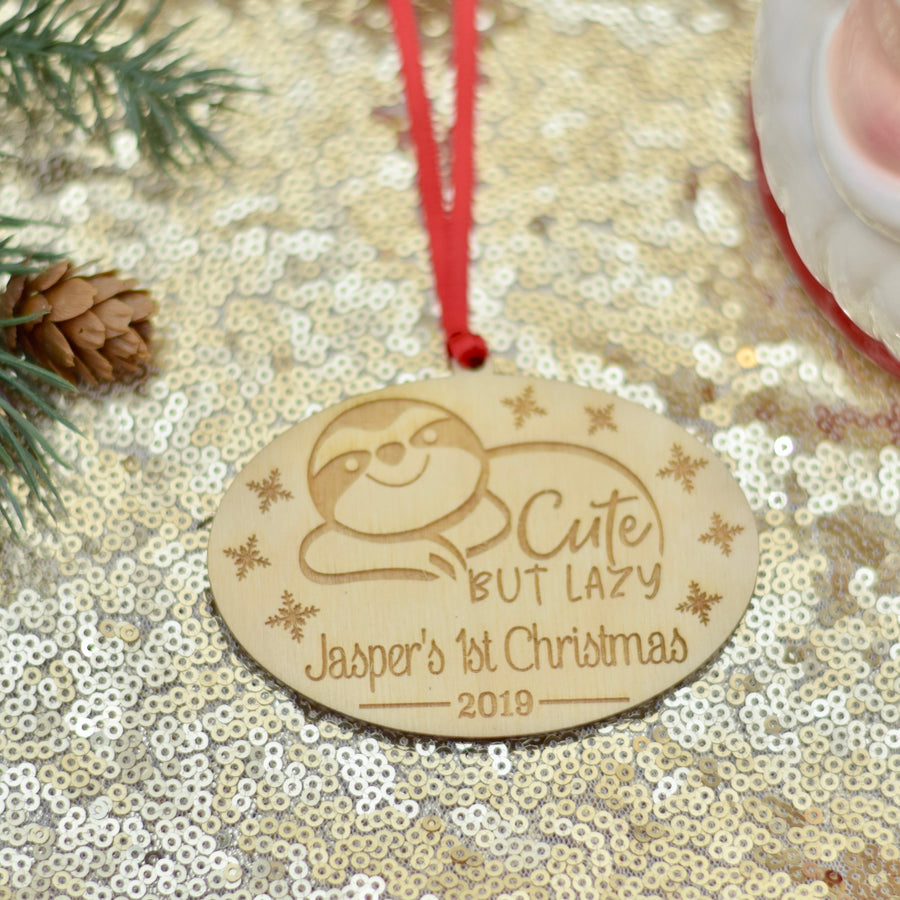 Baby's first Christmas ornament is a sloth that says Cute but lazy. Lying on a cake plate with greenery