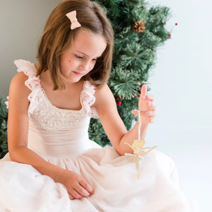 Little girl wearing pink dress holding ballerina Christmas ornament in front of green wreath
