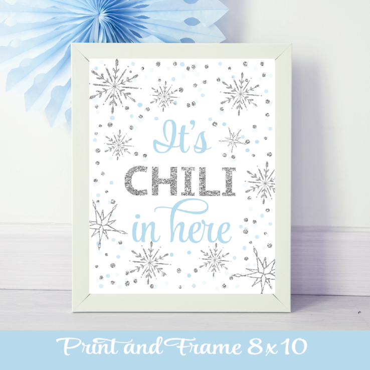 Blue and silver Its Chili in Here Sign in a white frame with a blue pinwheel on the wall
