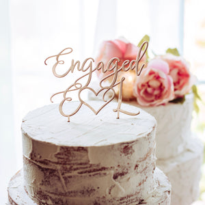 rose gold engaged cake topper on a white naked cake and pink flowers