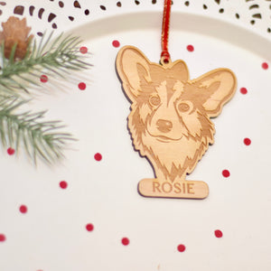 corgi dog ornament laser cut out of wood with christmas greenery and red confetti around it