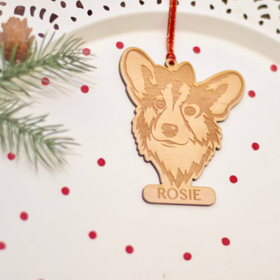 Corgi wooden ornament with a bowtie placed on a white cake plate with red confetti