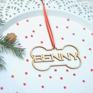 Benny Christmas tree ornament on a cake plate with greenery and red confetti