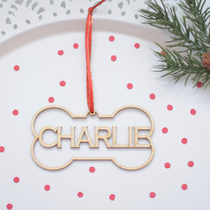 Charlie dog bone Christmas ornament on a white cake plate with red confetti and greenery