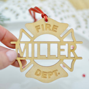 fireman gift for christmas ornament being held in a ladies hand