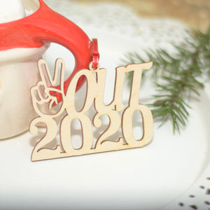 Peace out 2020 Pandemic Christmas ornament leaning on Santa mug