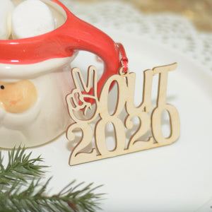 Wooden Peace Out 2020 Christmas ornament on a white plate with Santa mug