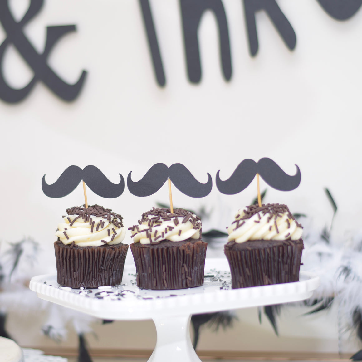 Set of three Black moustache cupcake toppers with three black and white cupcakes