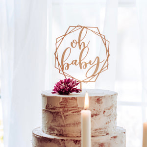 oh baby gender reveal cake topper on a cake with a candle in front of it