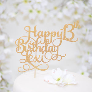 Gold happy 13th birthday cake topper on a white cake with white flowers