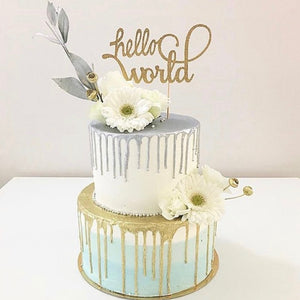 gold hello world cake topper on a silver mint and gold drip cake with daisies