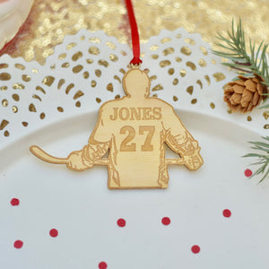 hockey jersey ornament with name and number on a white cake plate with red confetti