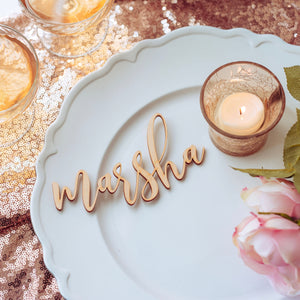name place card placed on white plate with candle at a wedding with rose gold table cloth