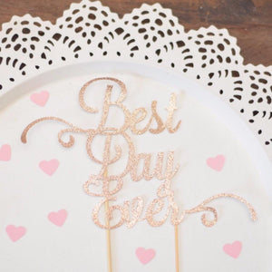 Best day ever gold sparkle glitter cake topper on white plate with pink heart confetti