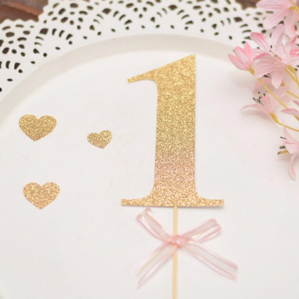 1 gold glitter cake topper on a white background with gold glitter heart accents