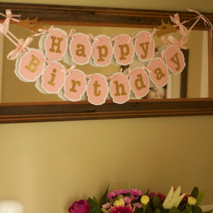 happy birthday pink and gold banner over a mirror
