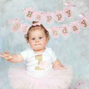 little girl wearing tutu in front of happy birthday banner