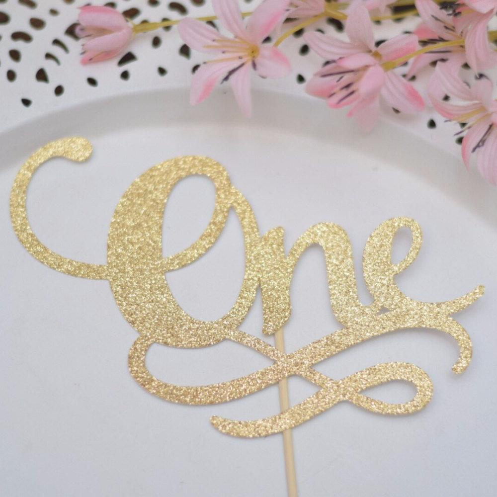 One gold sparkle glitter cake toppers with details on white plate