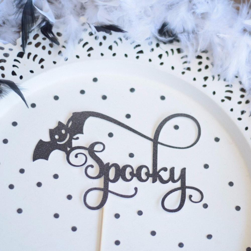 Spooky black sparkle cake topper with bat details and delicate details on a white plate background