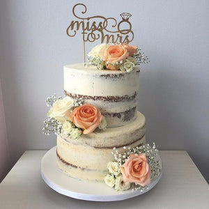 miss to mrs golden cake topper on an ivory cake with blush coloured flowers